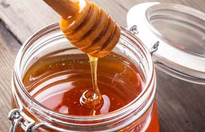 honey drizzling from honey spoon into glass jar