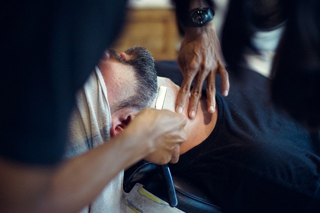 barber shaping the beard of his customer