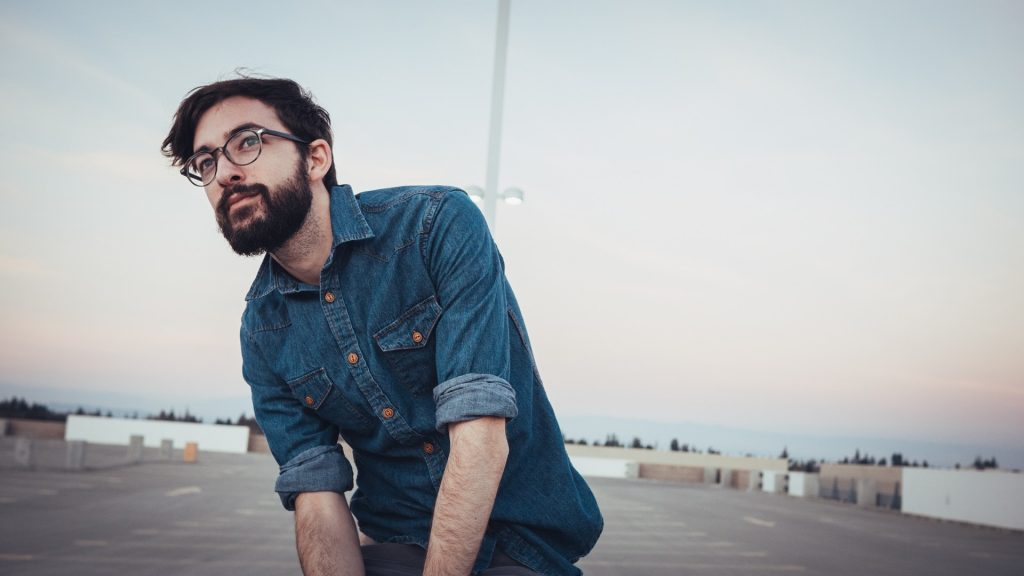 Photo of a man with beard wearing denim jacket
