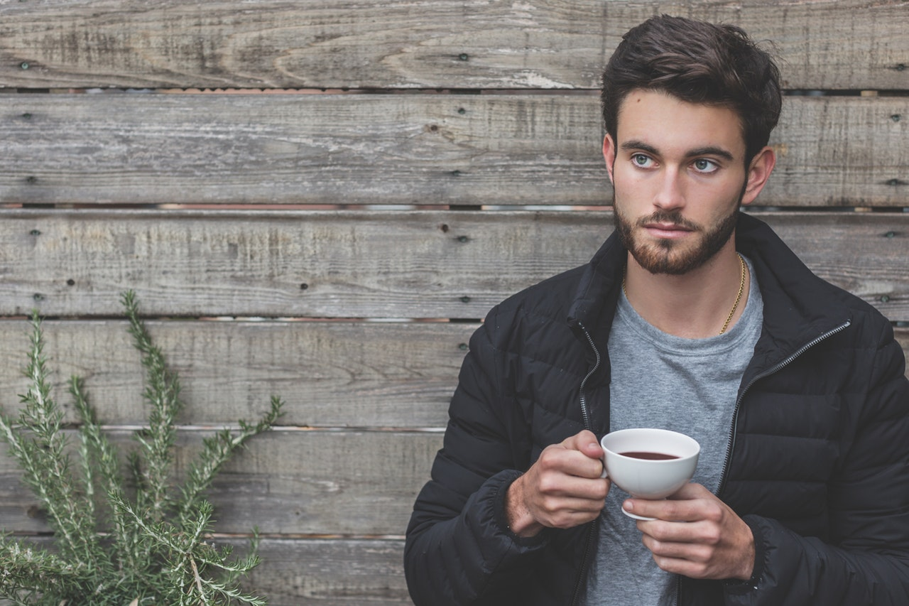 man with beard holding a cup of coffee