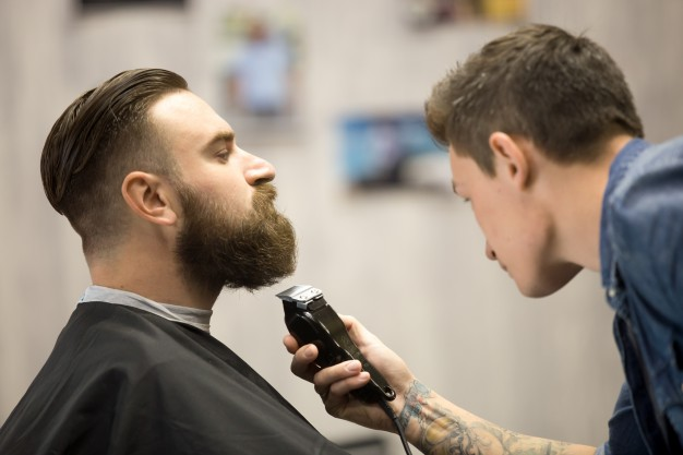 young man getting beard grooming