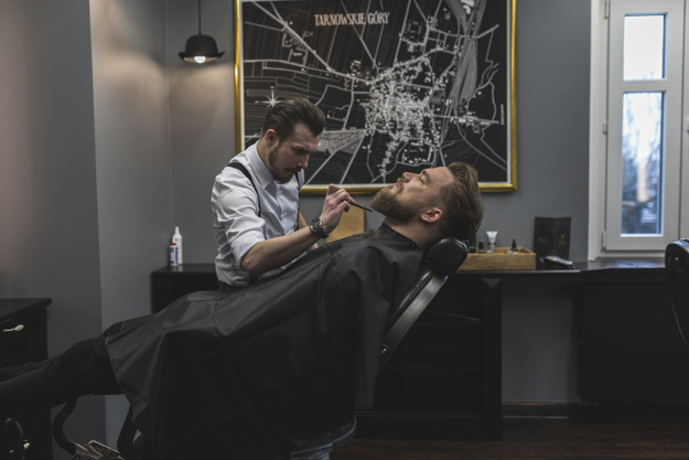 barber trimming beard of customer